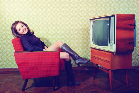 60s fashion: portrait of young smiling woman sitting in vintage room and watching tv, retro stylization, toned and noise added