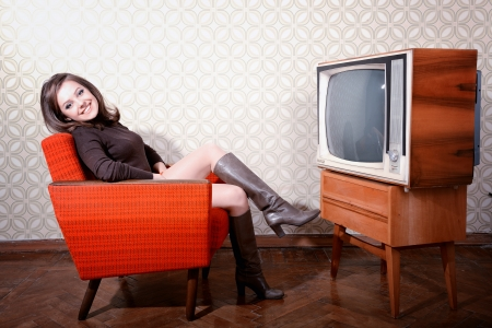 portrait of young smiling woman sitting in vintage room and watching tv, retro stylization, toned photo