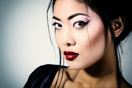 Young beautiful asian womans portrait, studio shot toned and noise added photo