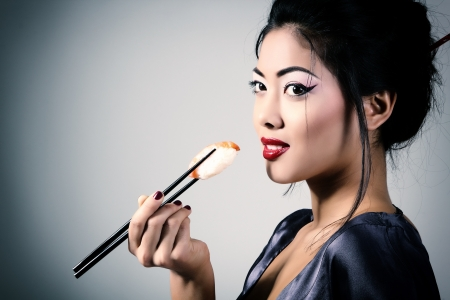 Young beautiful asian woman eating sushi with chopsticks, toned image