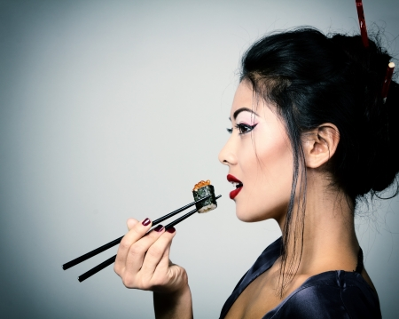 Young beautiful asian woman eating sushi with chopsticks, toned image and noise added