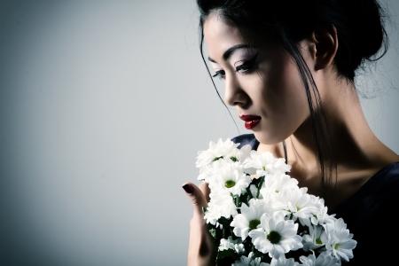 Young beautiful asian womans portrait with white flowers, studio shot toned Banco de Imagens