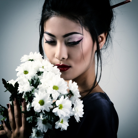 Young beautiful asian woman's portrait with white flowers, studio shot toned photo