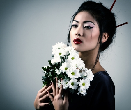 Young beautiful asian womans portrait with white flowers, studio shot toned and noise added