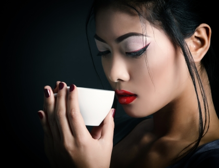 Young beautiful asian woman and tea ceremony, studio shot over black backround with copyspace photo
