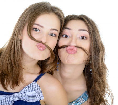 Portrait of a two teen girls have fun and make faces with moustache made of hair pigtail, isolated on white  photo