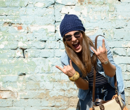 portrait of beautiful cool girl gesturing in hat and sunglasses over grunge wall