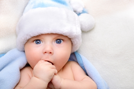 christmas cute baby boy, beautiful infant in Santas hat and blue soft plaid with vivid positive expression