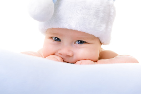 christmas cute baby boy lying on blue soft plaid like on snowdrift, beautiful infant in Santas hat Stock Photo