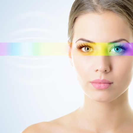 opthalmology: beautiful womans face with rainbow light on eyes Stock Photo