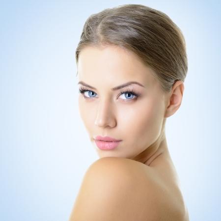 ojos hermosos: Retrato de una joven atractiva sobre fondo azul