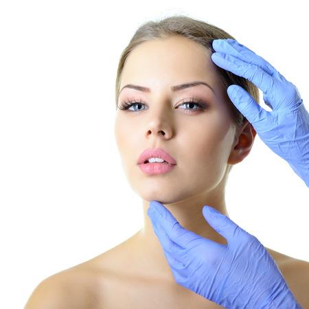 젊은 아름 다운 여성의 얼굴 미용 치료, 장갑 의사의 손을 흰색에 고립 된 아름 다운 젊은 여자의 얼굴을 만지지