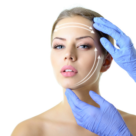 plastic glove: facelift, beauty treatment of the young beautiful female face, doctors hand in gloves touch face of beautiful young woman isolated on white