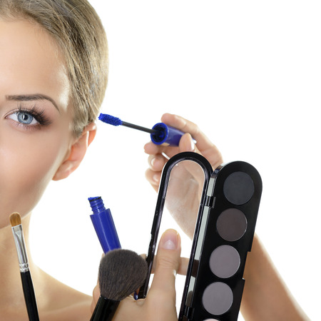 Part of face of beautiful young woman with brushes and cosmetics, over white photo