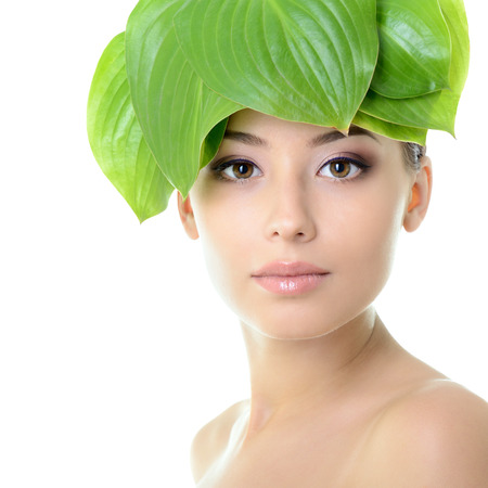 beautiful young cheerful woman with green leaves near her face, care of nature concept, over white background photo