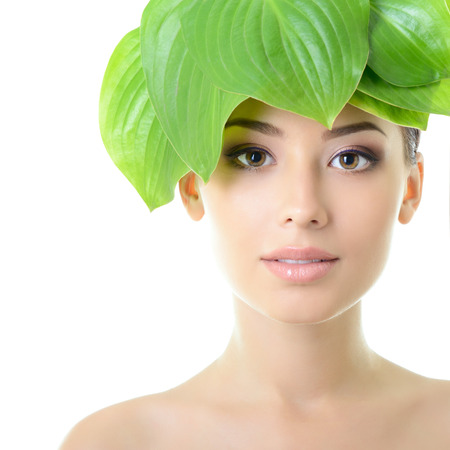 beautiful young cheerful woman with green leaves near her face, care of nature concept, over white background Stockfoto