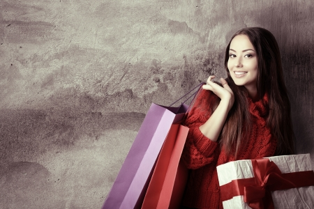 beautiful young woman holding colored shopping bags and gift box over grunge concrete wall, holiday seasonal concept, toned photo
