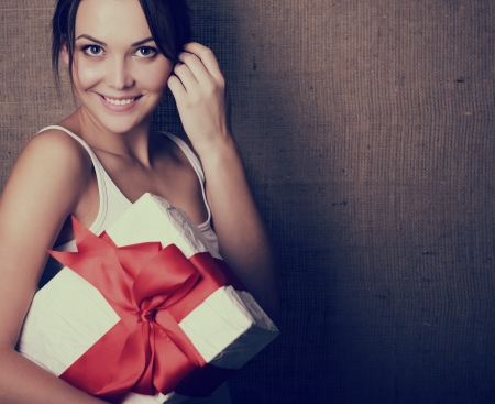 Portrait of attractive cheerful girl in sleeveless sports white shirt holding gift box with red bow over canvas background, toned