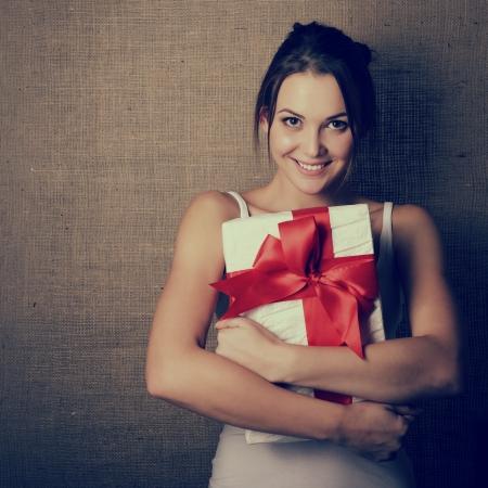 Portret van aantrekkelijke vrolijke meid in mouwloze sport wit overhemd bedrijf geschenk doos met rode strik op doek achtergrond, afgezwakt en ruis toegevoegd