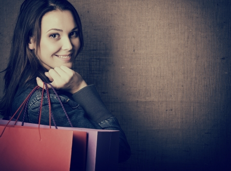 Portrait of beautiful girl holding colored shopping bags, toned  photo