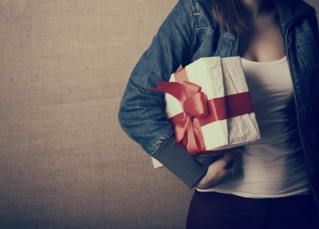 Portrait of attractive cheerful girl holding gift box with red bow over canvas background, toned photo
