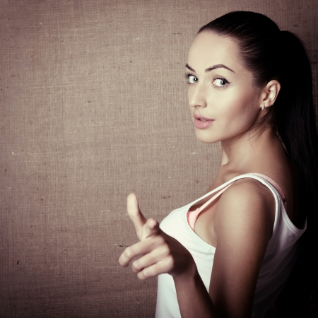1 young woman only: Portrait of young woman pointing with finger at viewer, over canvas background, toned