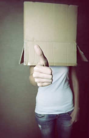faceless girl with box on her head LIKE with thumb up, social network concept, toned photo