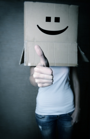 thoughtless: faceless girl with box on her head LIKE with thumb up, social network concept, toned Stock Photo