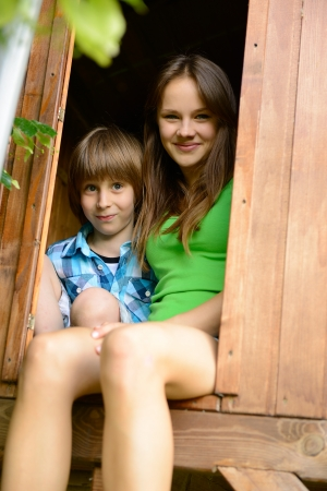 outdoor portrait of cheerful attractive teen girl playing with her little brother in garden wooden house photo