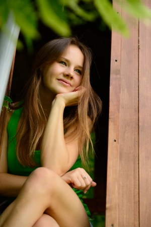 outdoor portrait of cheerful attractive teen girl in garden wooden house photo