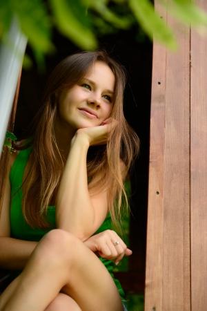niña: Retrato al aire libre de la alegre atractiva muchacha adolescente en el jardín de casa de madera