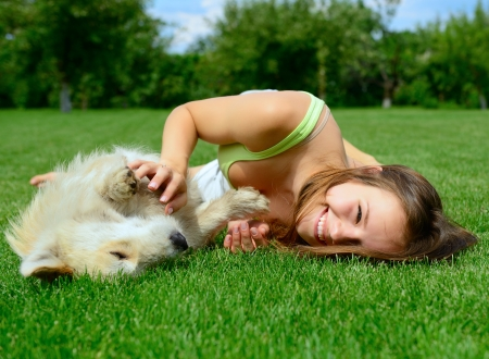 beautiful young happy laugh girl playing with her dog outdoor photo