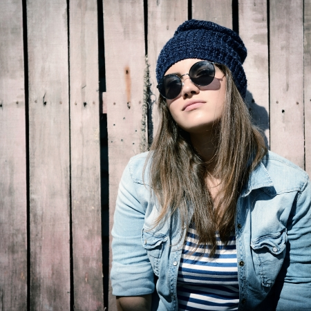 beautiful cool girl in hat and sunglasses against grunge wooden fence, toned photo