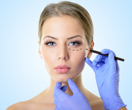 Beautiful woman ready for cosmetic surgery, female face with doctor's hands drawing lines on skin, over blue photo