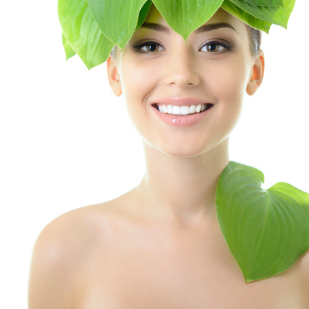 beautiful yoiung cheerful woman with green leaves near her face, over white background