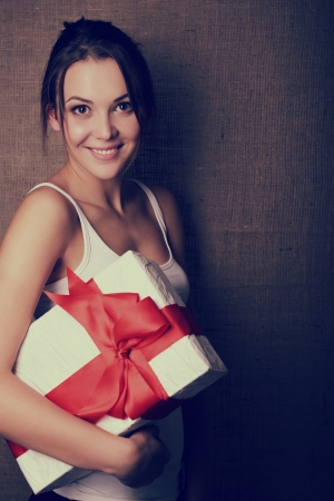 Portrait of attractive cheerful girl in sleeveless sports white shirt holding gift box with red bow over canvas background, toned photo
