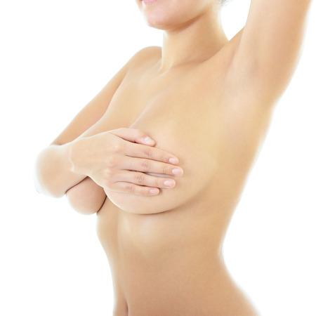beaux seins: Corps de belle femme couvrant sa poitrine et en montrant l'aisselle, sur fond blanc Banque d'images