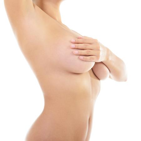 beaux seins: Corps de la belle femme couvrant sa poitrine et en montrant l'aisselle, sur fond blanc Banque d'images
