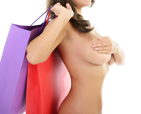 Beautiful young nude woman holding shopping bags covering her brest, over white background photo
