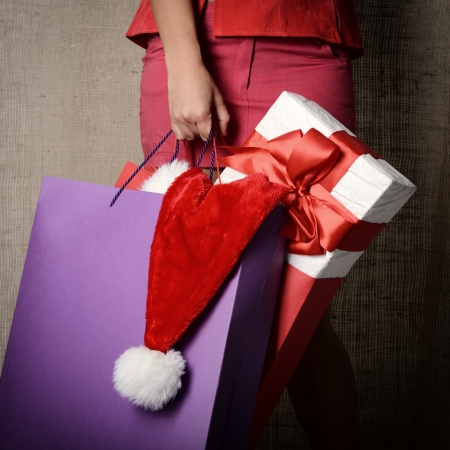 Beautiful young woman holding colored shopping bags, gift box and Santas hat over canvas background, glamour shopping concept, image toned  photo