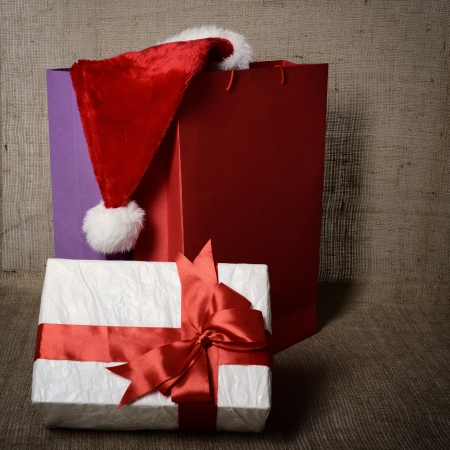 hristmas: Ð¡hristmas gift box with colored bags and Santas hat over canvas background, holiday shopping concept