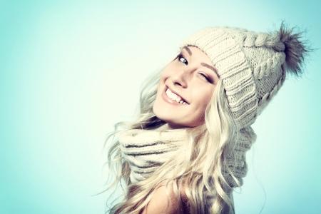 beleza: menina natal, sorriso bonita e dar uma piscadela sobre o fundo azul