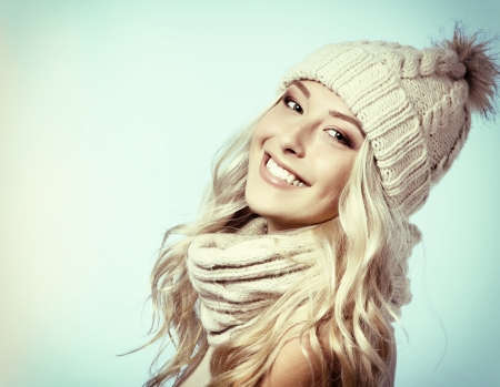christmas girl, young beautiful smiling and give a wink over blue background, toned