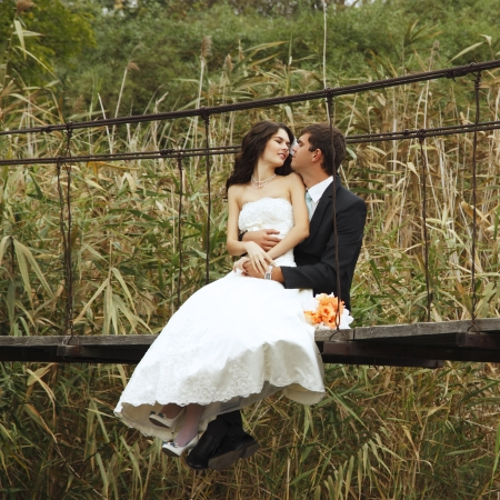young wedding couple, beautiful bride with goom portrait on the bridge, summer nature outdoor photo