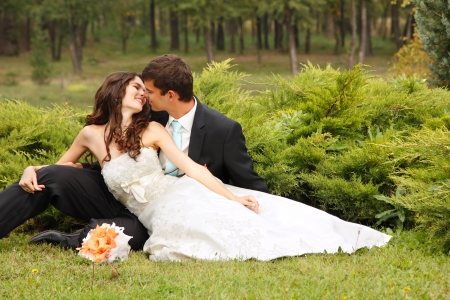 love kissing: wedding, beautiful young bride lying together with groom in love on green grass kissing, park summer outdoor