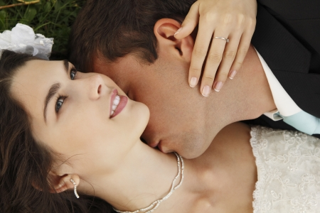 wedding, beautiful young bride lying together with groom in love on green grass kissing, park summer outdoor photo