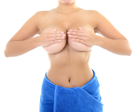 naked belly: Body of beautiful woman covering her breast with hand in blue towel, over white
