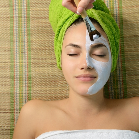 Beautiful young woman having facial mask apply by beautician in salon Stock Photo