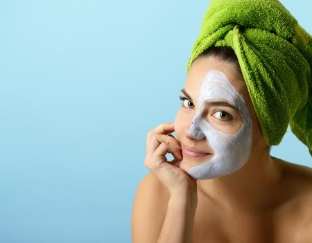 antifaz: Joven y bella mujer con máscara facial, tratamientos de belleza sobre azul Foto de archivo