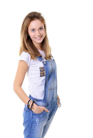 overol: Muchacha adolescente alegre hermosa en azul denim catsuit mirando la cámara y sonriendo feliz. Aislado en el fondo blanco